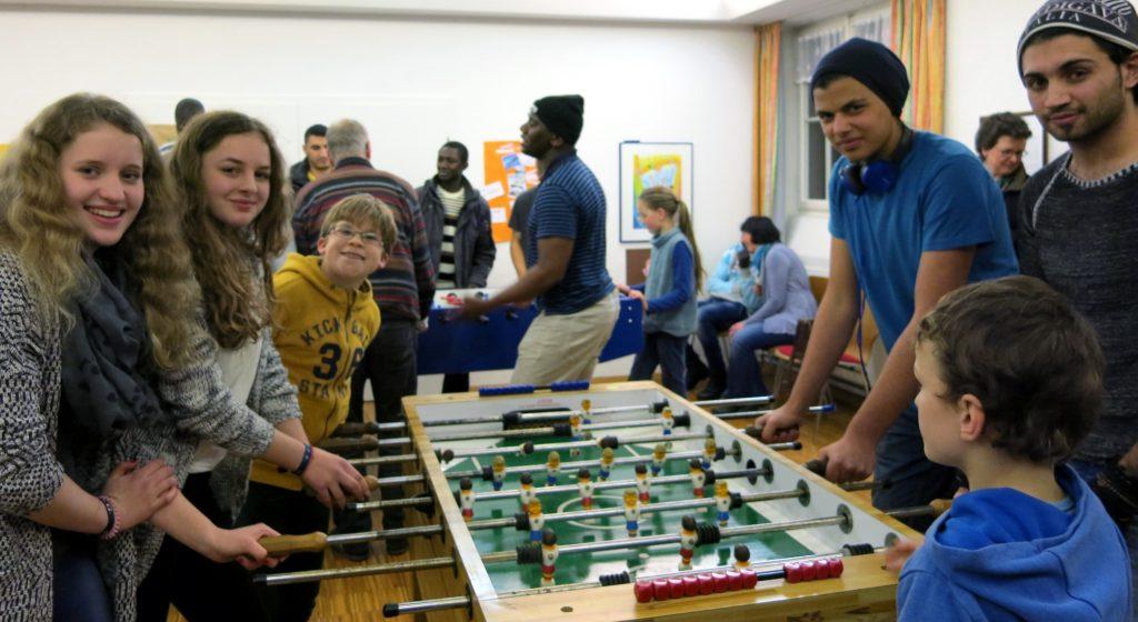Asylbewerber und Gemeindemitglieder, darunter viele junge Leute, beim Tischfußball. Foto: Birgit Selletin